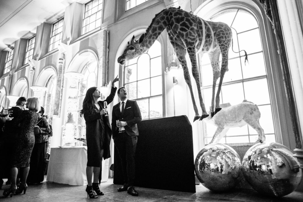 A photo of two wedding guests looking at the taxidermy giraffe at Aynhoe Park which hangs from the ceiling on the orangery