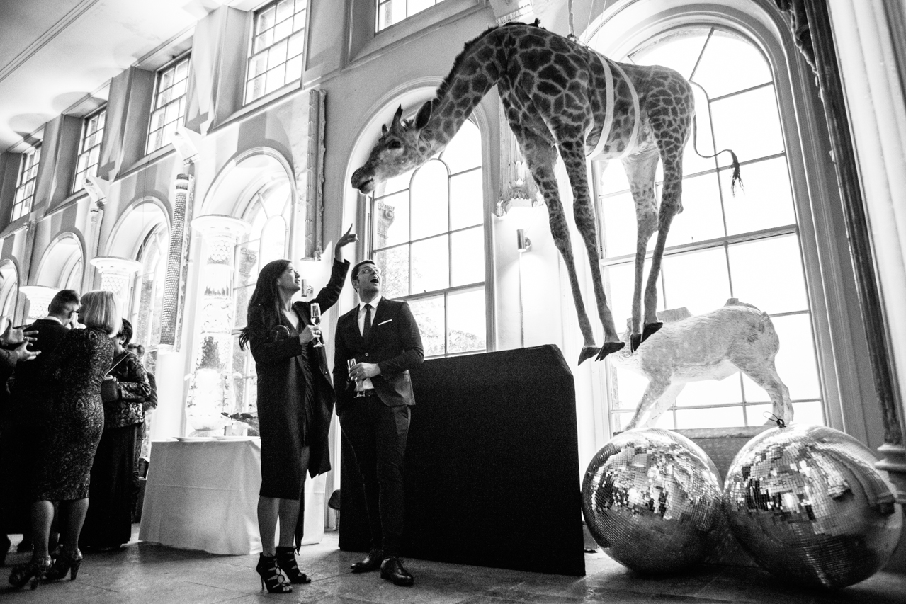 A black and white photography of wedding guests looking aghast at a full size taxidermy giraffe hanging from the ceiling at Aynhoe Park wedding venue