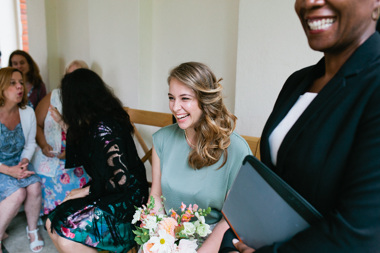 A candid portrait of a wedding guest smiling durring a ceremony at The Hill Top Gardens and Pergola Wedding on Londons Hampstead Heath - Kent documentary wedding photography