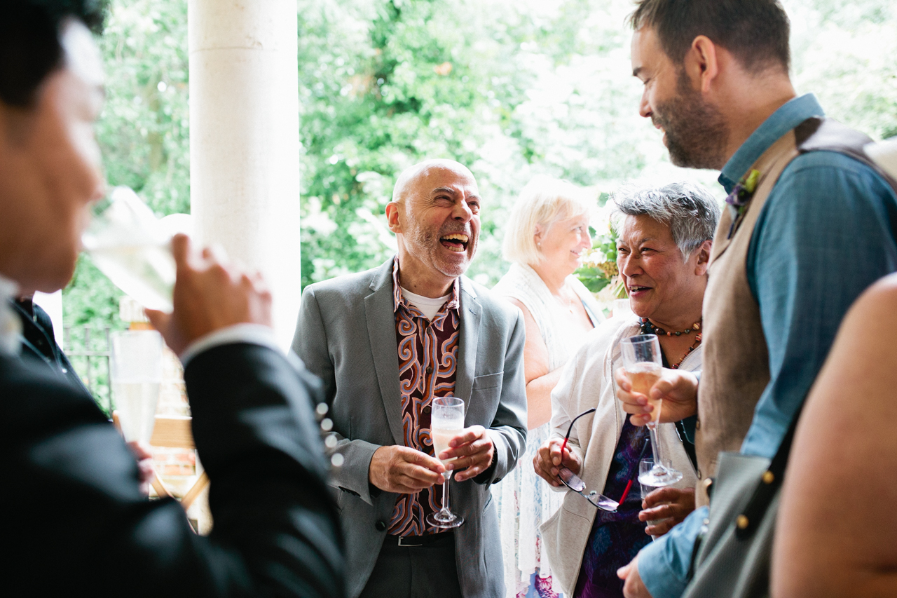 A smiling and lauging wedding guest at The Hill Top Gardens and Pergola Wedding on Londons Hampstead Heath - Kent documentary wedding photography