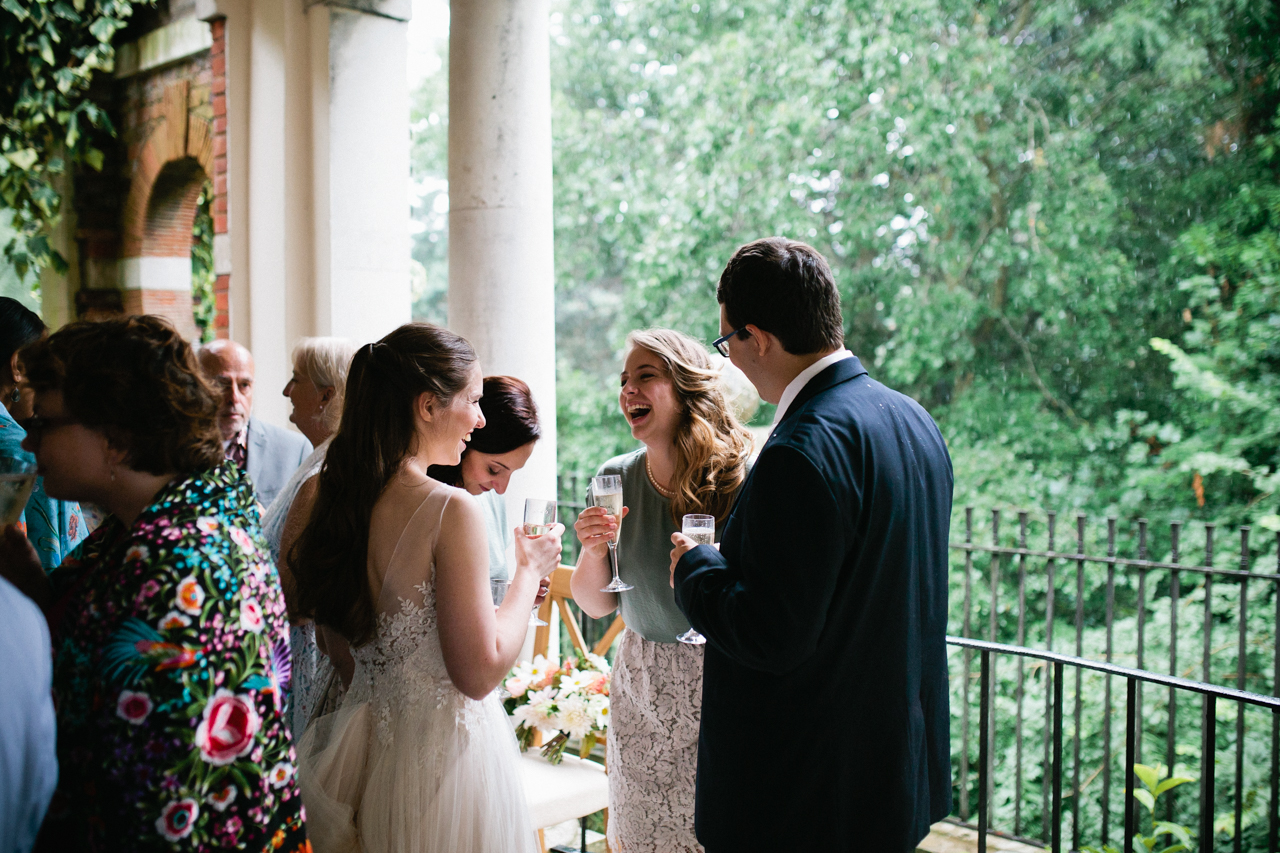 A candoid shot of wedding guests having fun at a wedding reception at The Hill Top Gardens and Pergola Wedding on Londons Hampstead Heath - Kent documentary wedding photography