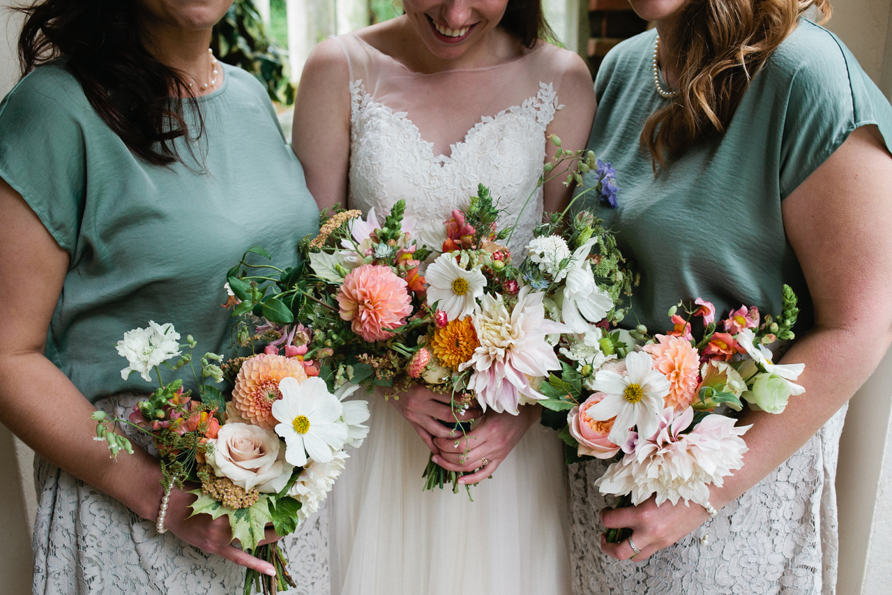 A beautiful and bride and her bridesmaids holding their wedding bouquets at The Hill Top Gardens and Pergola Wedding on Londons Hampstead Heath - Kent documentary wedding photography