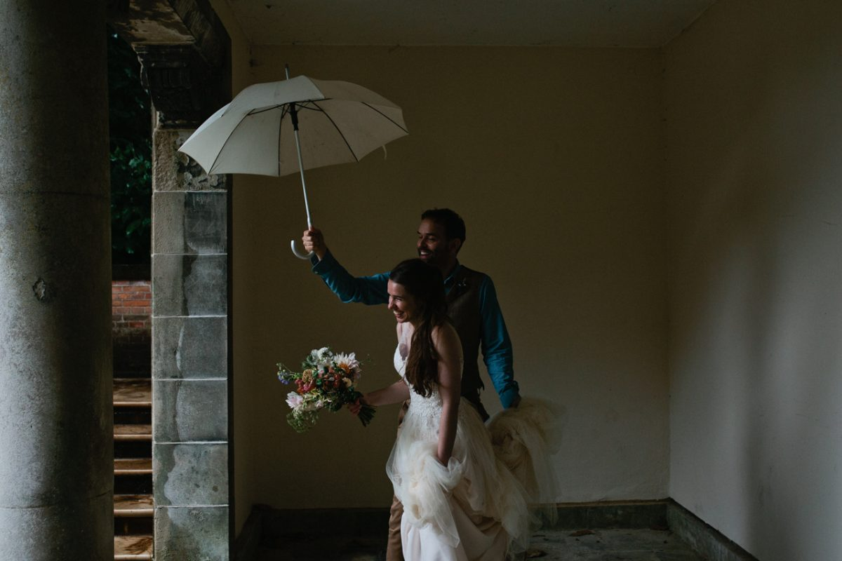A bride and groom shelter from the rain at their Hampstead Heath London wedding at The Hil Top Gardens and Pergola photographed ny natural documentary London and Kent Wedding Photographer Matilda Delves