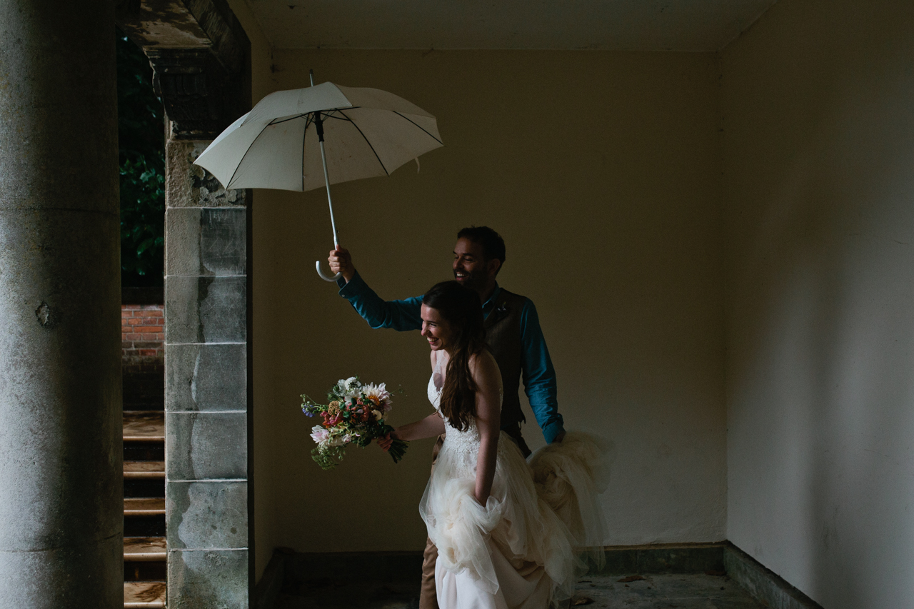 A grrom holds up an umbrella for his bride A beautiful and bride and her bridesmaids at The Hill Top Gardens and Pergola Wedding on Londons Hampstead Heath - Kent documentary wedding photography
