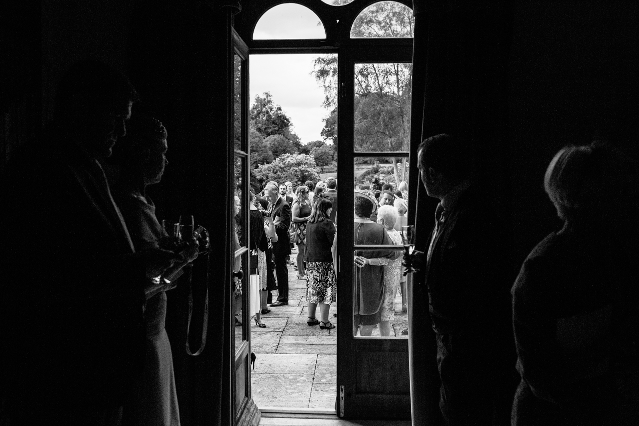 Black and white photography of wedding guest enjoying the grounds a wedding at an Englefield Estate – Kent Documentary wedding photography