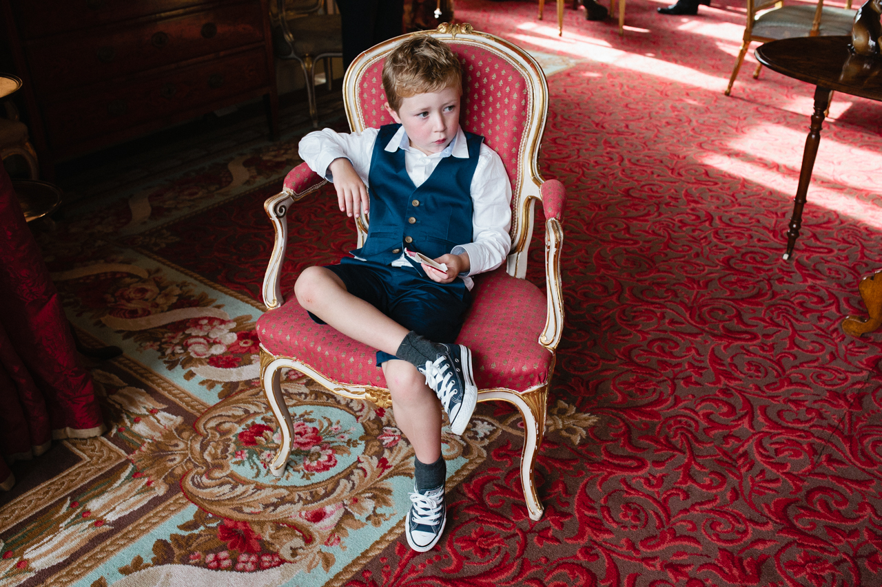 Colour photography of a page boy lounging in a chair at an Englefield Estate wedding – Kent Documentary wedding photography
