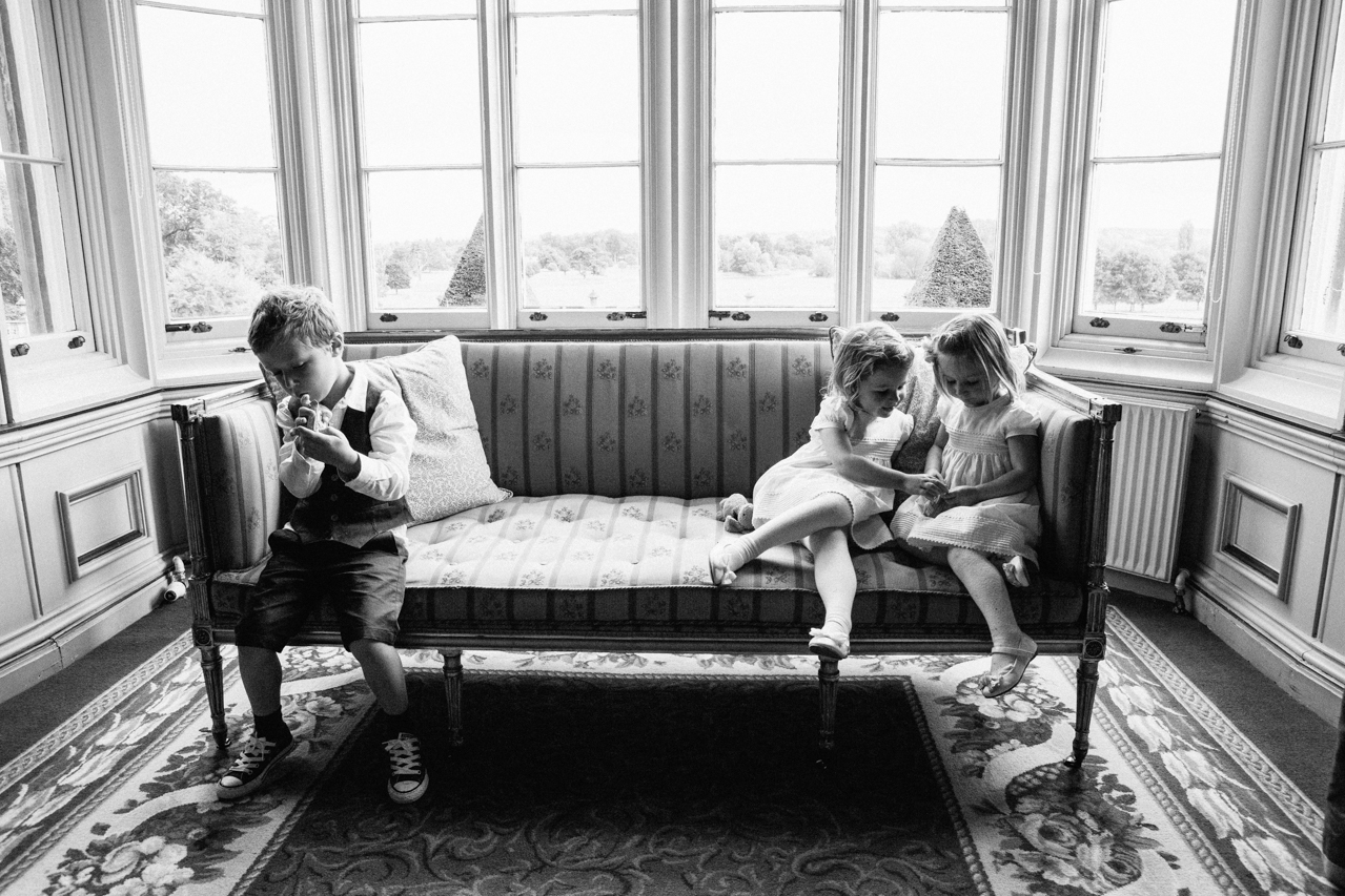 Black and white photography of naughty flowers girls ans a page boy in one of the main rooms at a wedding at Englefield Estate – Kent Documentary wedding photography