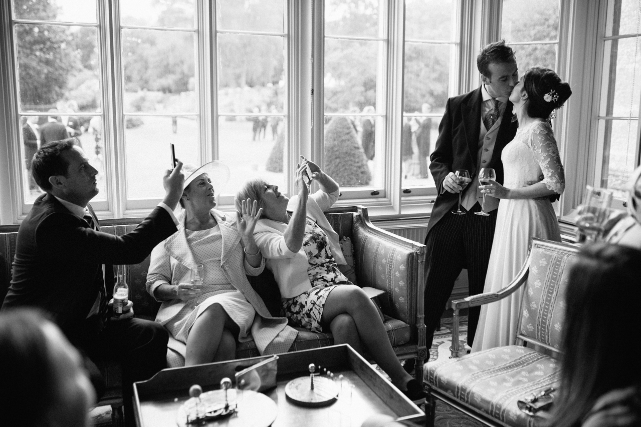 Black and white photography of a bride and groom being papped by their guest with iPhones at a wedding at Englefield Estate – Kent Documentary wedding photography