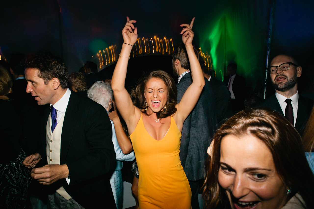 Colour photography of a striking young woman dancing energetically at an Englefield Estate wedding – Kent Documentary wedding photography
