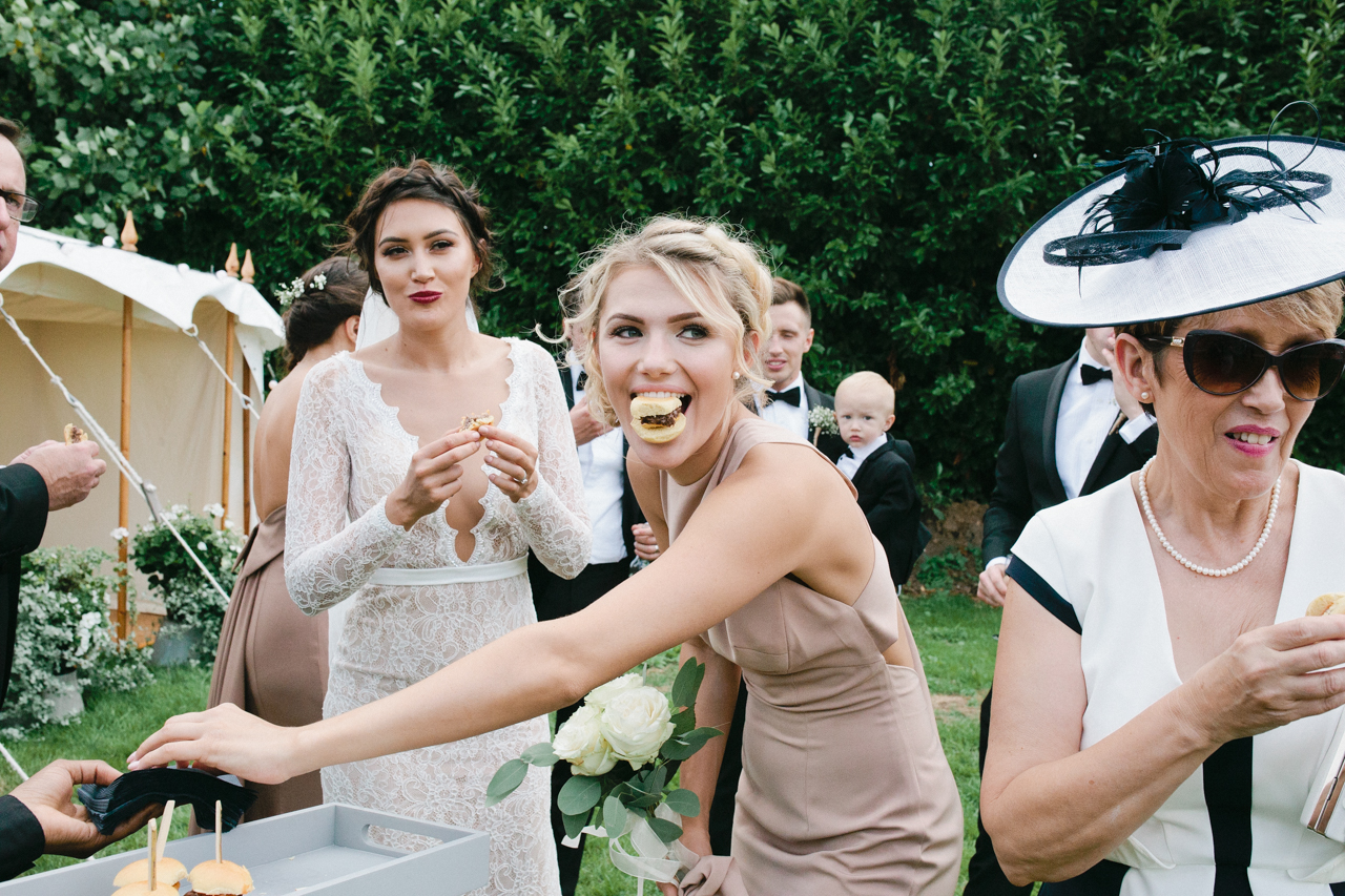 Colour photograph of a wedding guest with a mini hamburger in her mouth - Kent Documentary wedding photography