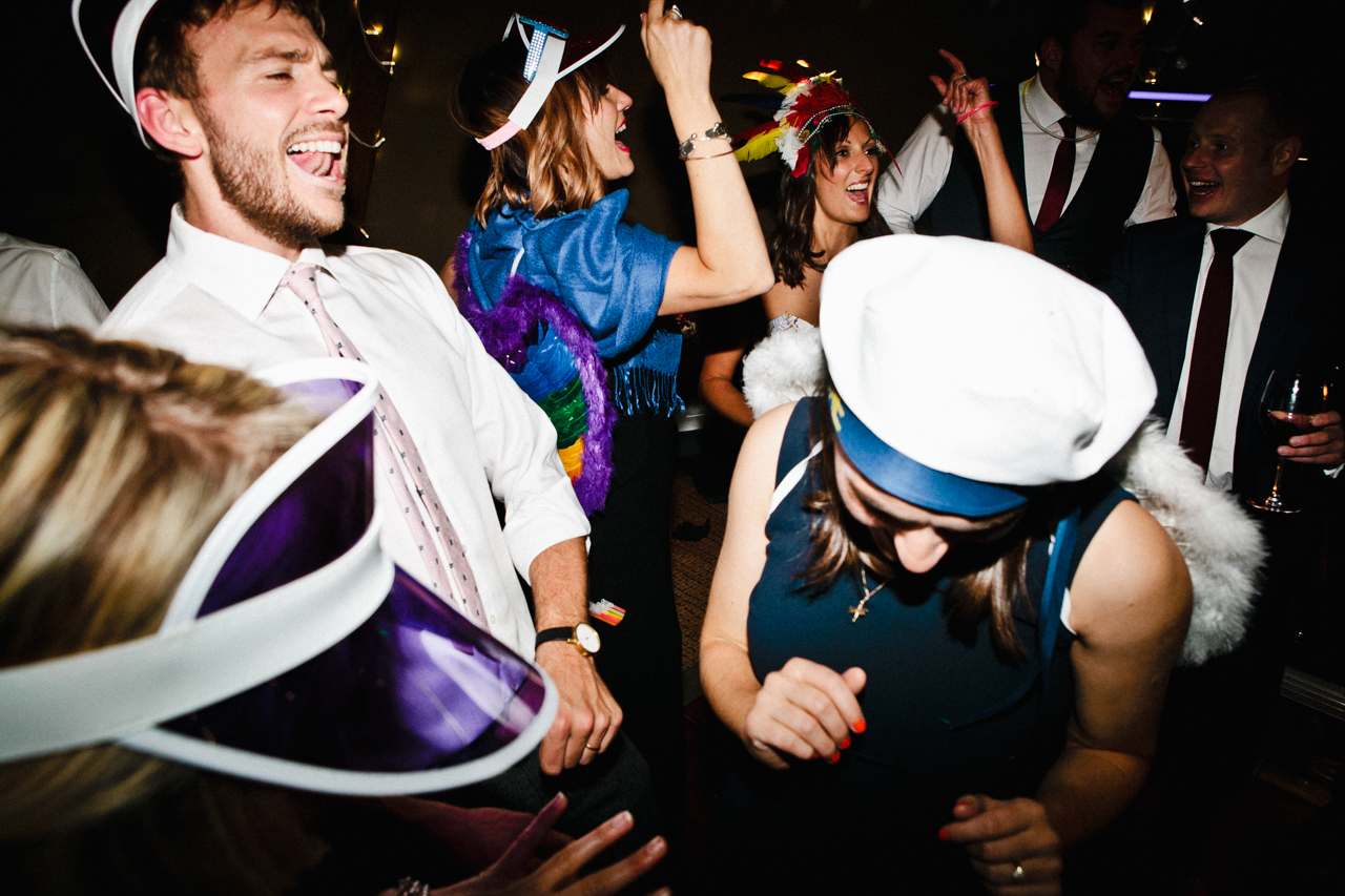 Colour photograph of wedding guests dancing on a dance floor while wearing different fancy dress at a tipi wedding in Kent - Kent Documentary wedding photography