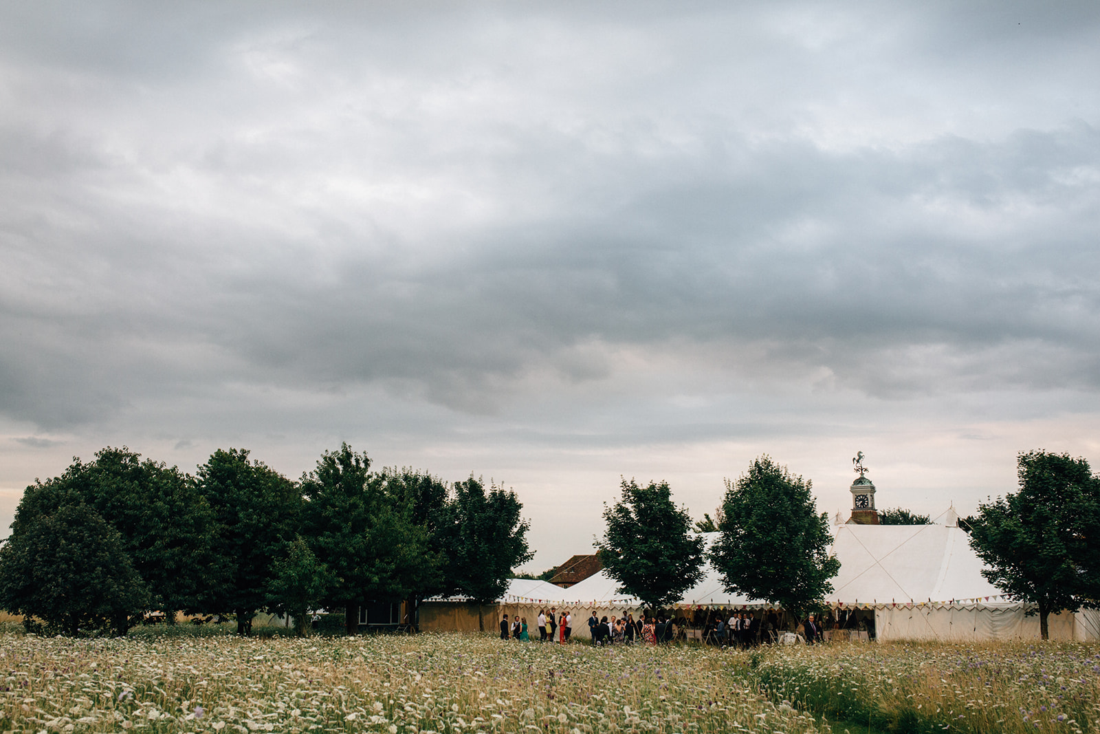 A beautiful photograph of a House of Hud marquee set up in a meadow by Kent marquee weddings photographer Matilda Delves who is a Kent Wedding Photographer who specialises in natural wedding photography