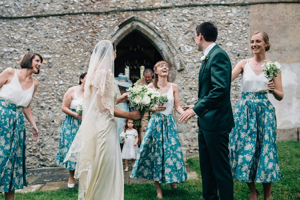 A natural documentary wedding photograph of a bride and groom with their bridesmaids at a marquee by Kent marquee weddings photographer Matilda Delves