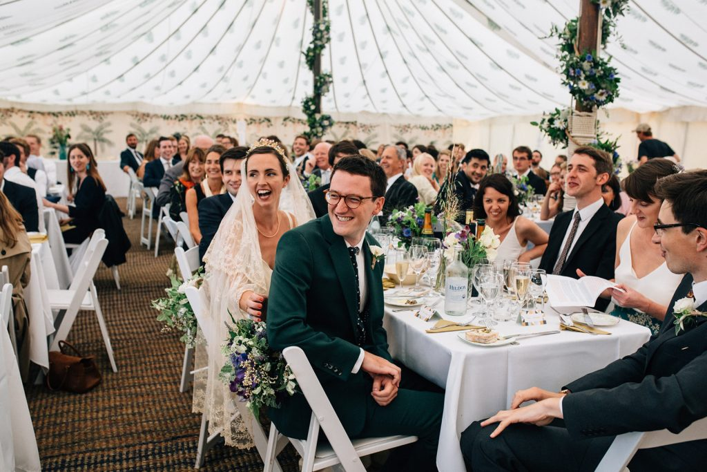 A natural documentary wedding photograph of a bride and groom in a marquee by Kent marquee weddings photographer Matilda Delves who photographs weddings in a natural style