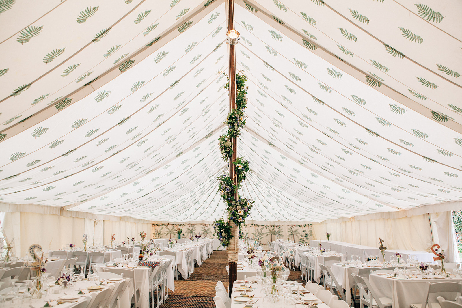 A beauifully decorated House of Hud summer marquee wedding on a farm near Canterbury by Kent Marquee Weddings Photographer Matilda Delves