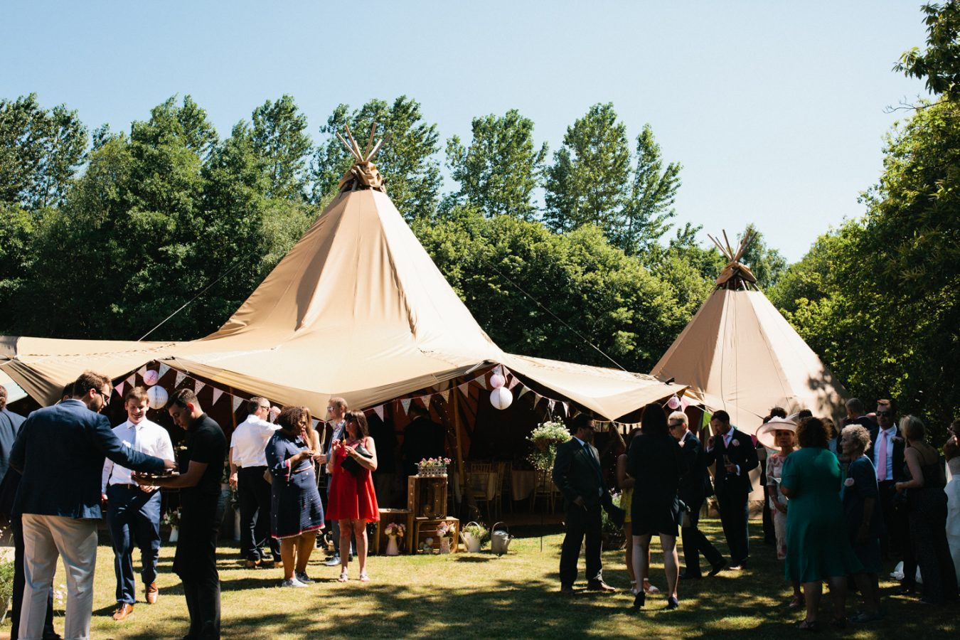 Wedding guests enjoying a beautiful Tipi Weddings in Kent by Kent Wedding Photographer Matilda Delves who specialises in natural wedding photography in Kent and Sussex
