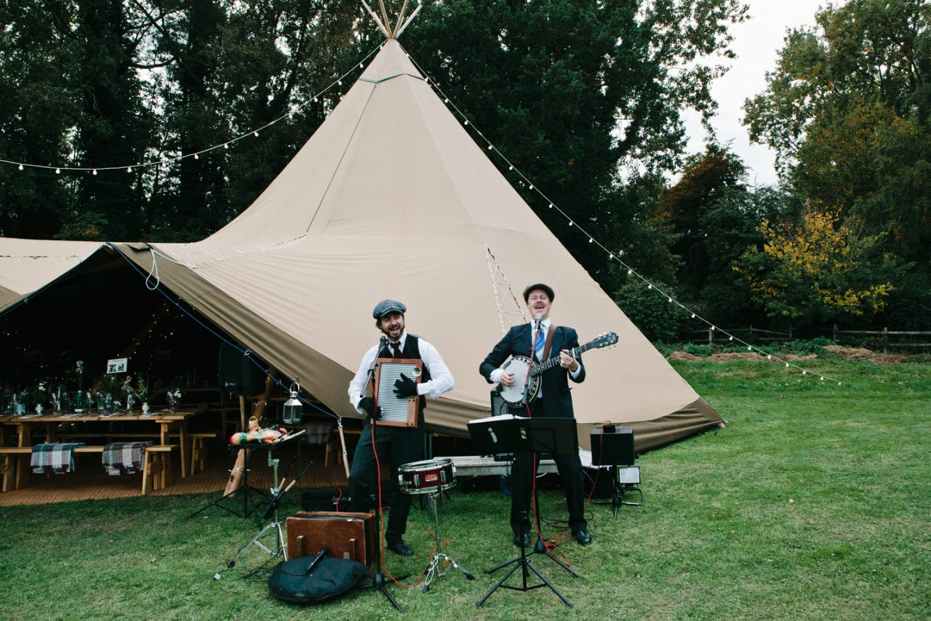 A photograph of a band playing music outside of a Tipi wedding in Kent photographed by London and Kent wedding photographer Matilda Delves who specialises in natural wedding photography in Kent
