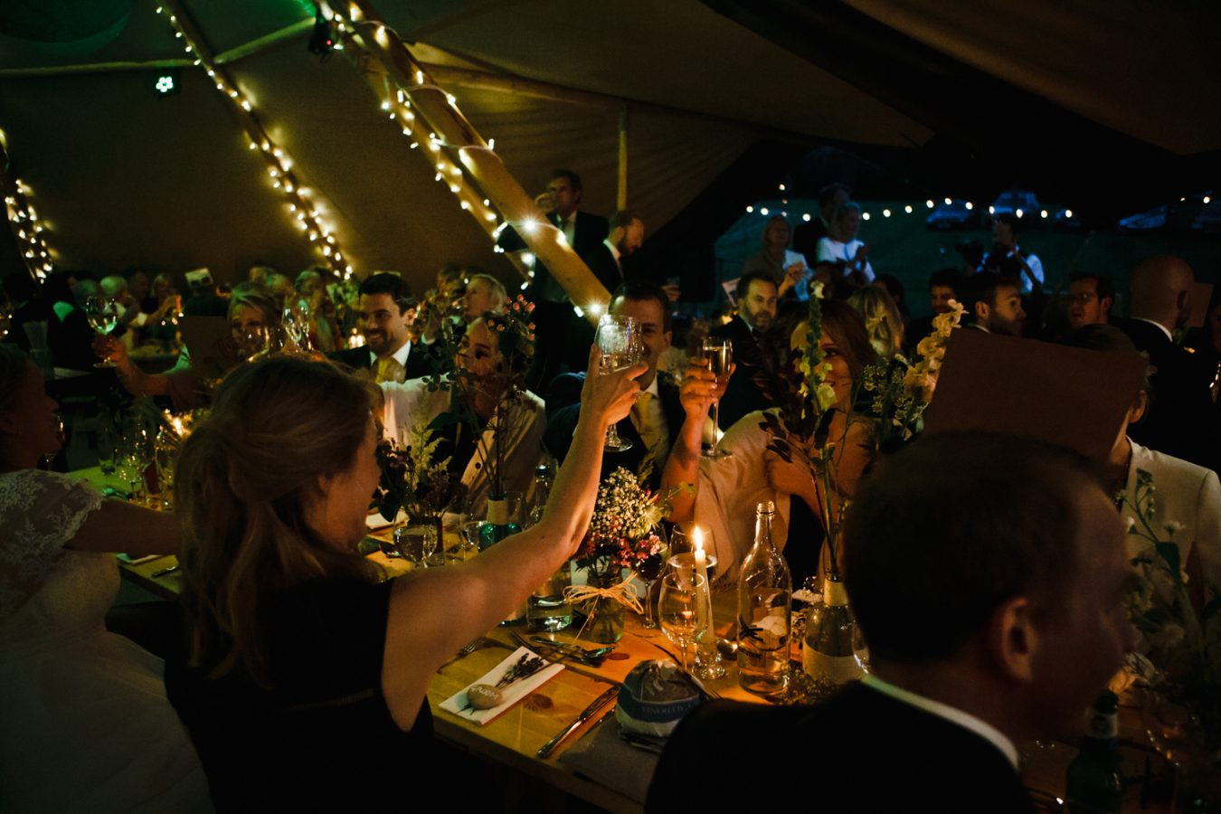 An atmospheric photograph of wedding guests making a toast at a Tipi Weddings in Kent and East Sussex by Kent Wedding Photographer Matilda Delves who specialises in natural wedding photography in Kent and Sussex