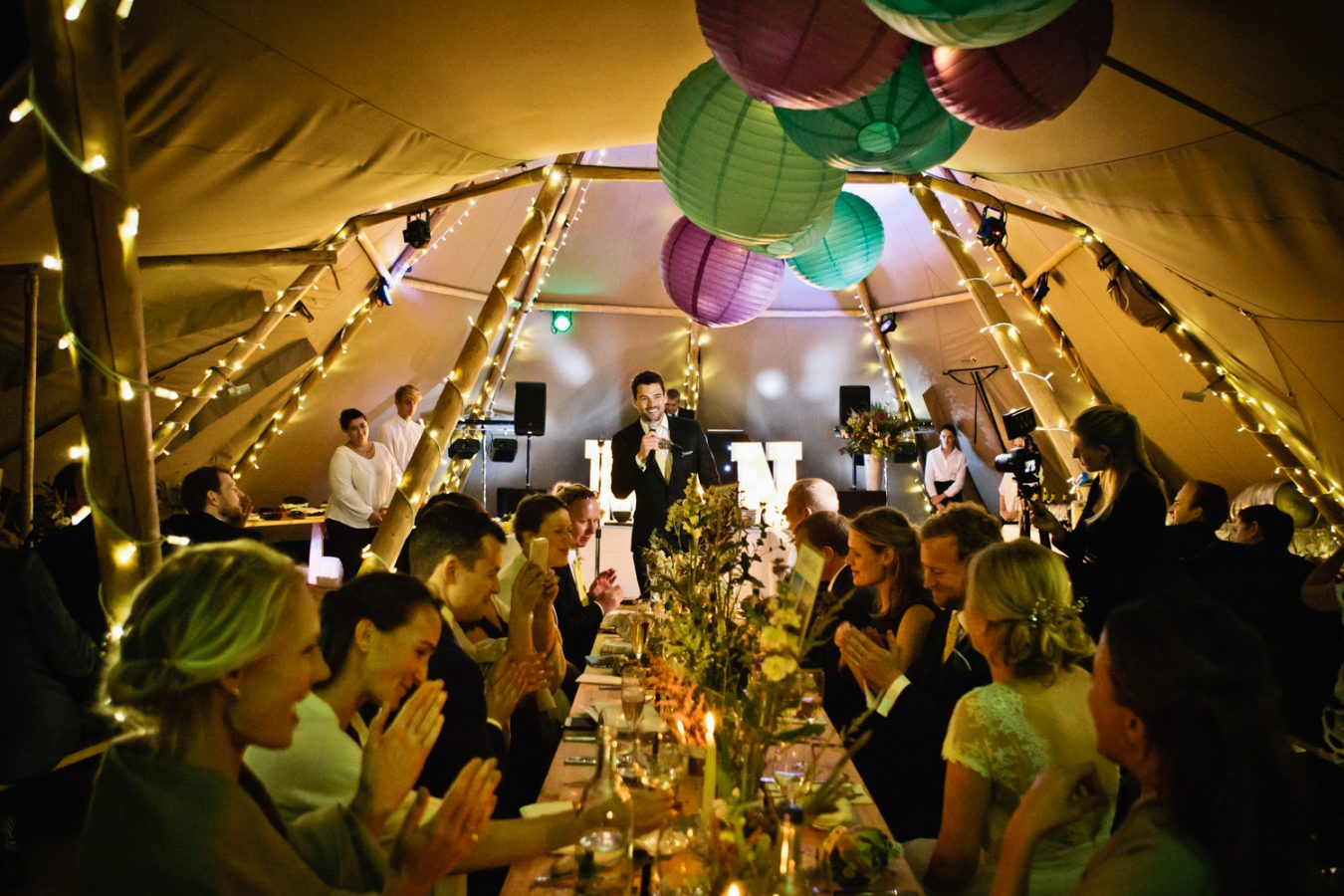 Photograph of a best man giving a speech at a Tipi Wedding in Kent, photographed by Natural Kent Wedding Photographer Matilda Delves who specialises in natural wedding photography in Kent