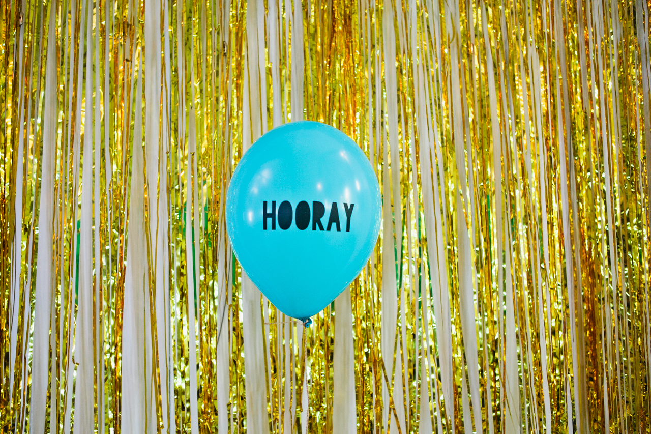 Wedding ballon with Hooray written on a balloon in-front of a gold glittery backdrop at a village hall wedding in Canterbury bu natural Kent wedding photographer Matilda Delves