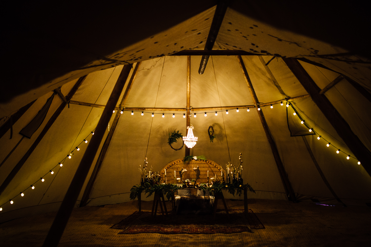 A bride standing in the doorway of a Tipi at the Wilderness Wedding Venue In Kent in this photo that talks about the top five woodland wedding venues in Kent and Sussex by natural style Kent Wedding photographer Matilda Delves