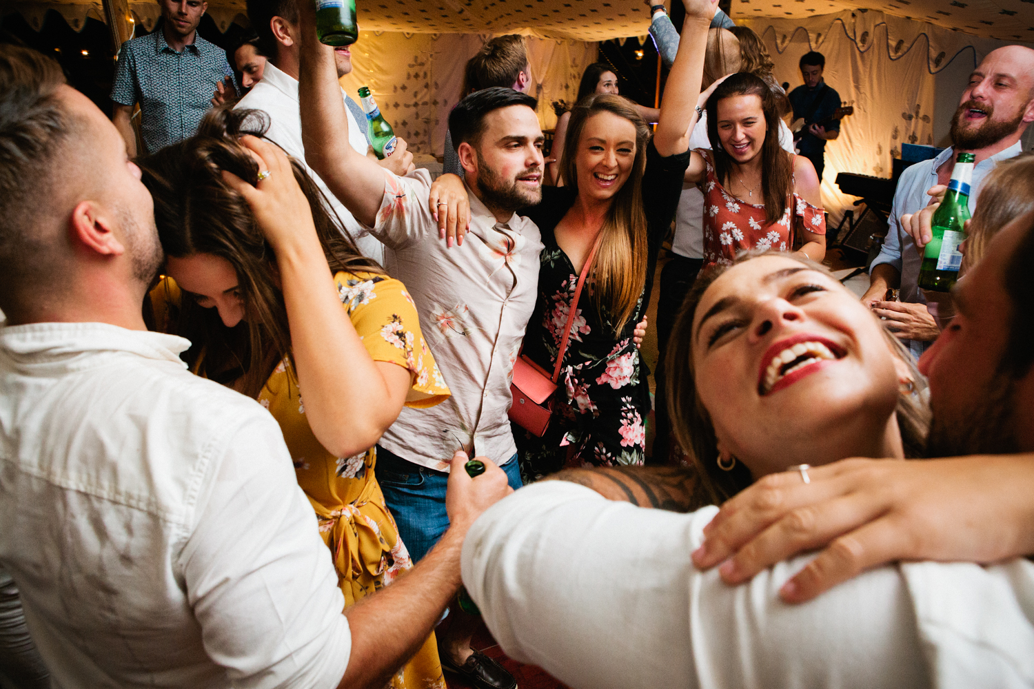 A group of drunk wedding guests dancing on the dance floor at a festival wedding in this guide on how to plan a festival wedding by Matilda Delves a Kent wedding photographer who specialises in natural wedding photography Kent
