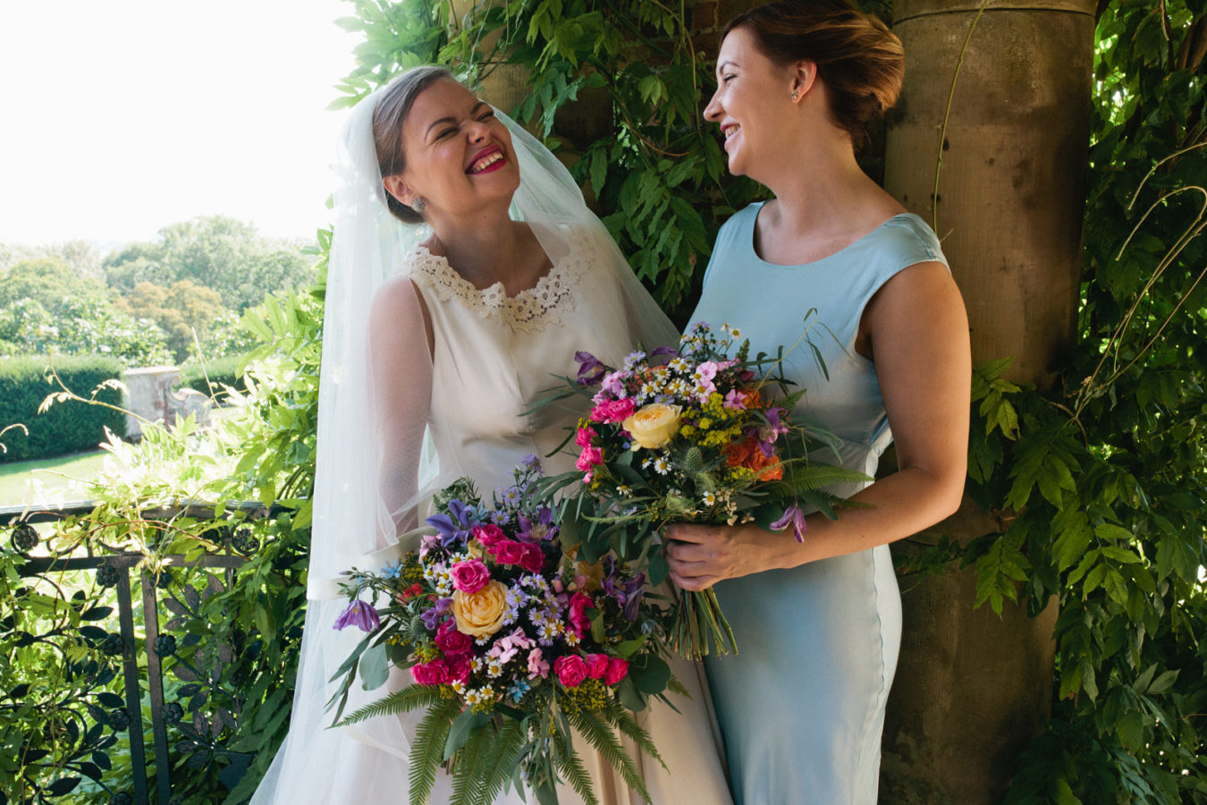 A bride and her bridesmaid laughing at Port Lympne Hotel