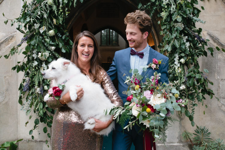 A bride who is wearing a sequin wedding dress holds her pet dog in her arms at her London Wedding
