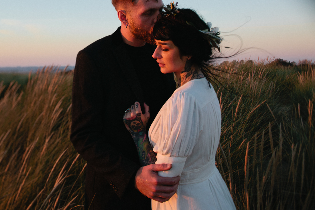 A photograph of a tattooed bride and groom in the dunes at Camber Sands by Kent Wedding Photographer Matilda Delves