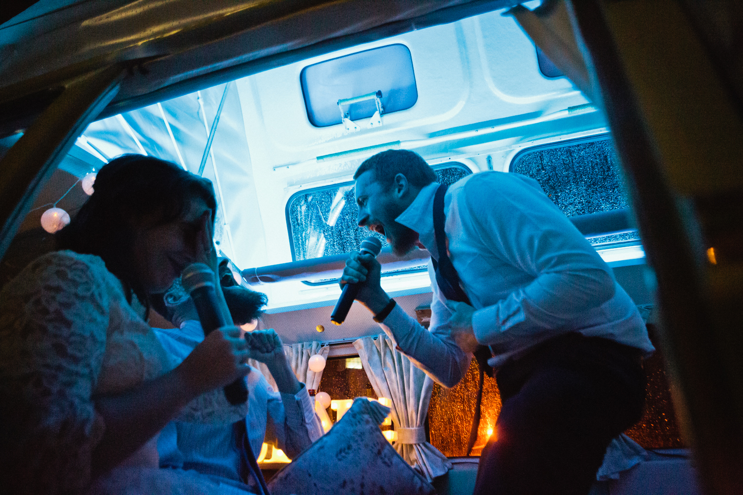 Wedding guests singing in a karaoke vw camper van called Mc Trigg outside of a winter wedding reception at the County Hall in Kingston Upon Thames, London