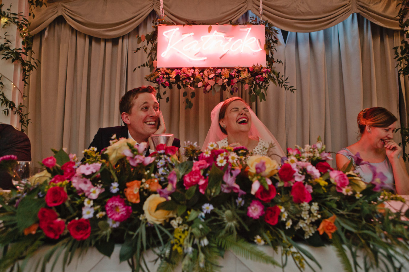 A bride and groom laughting durring the speecehd at their Port Lympne wedding
