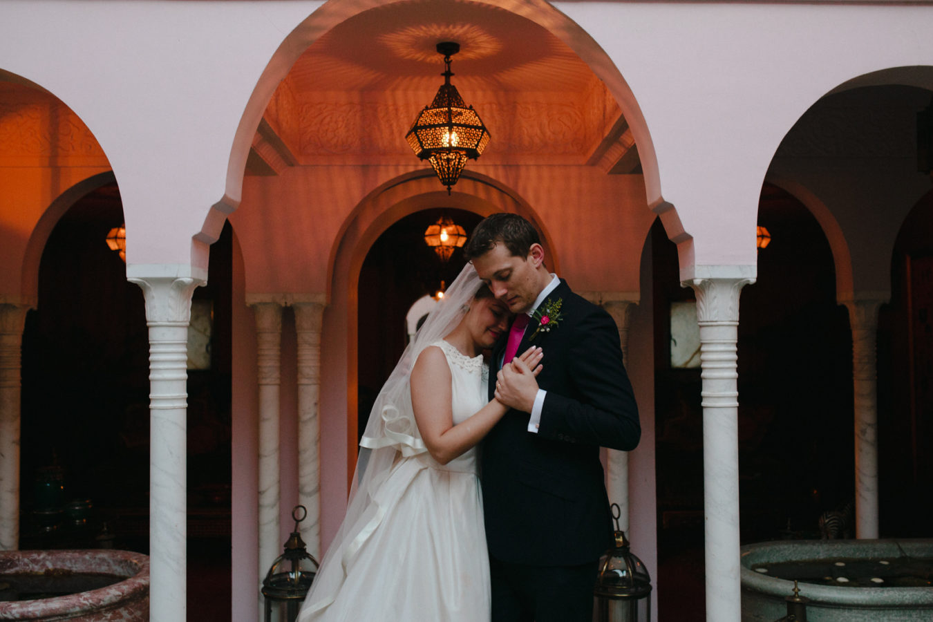 A natural photo of a bride and groom in the moroccan court yard at Port Lympne