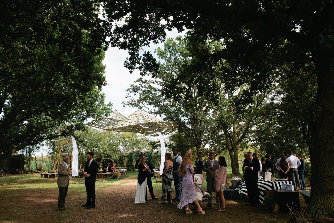 Wedding guests shelter from the sun under a parachute hung from the trees at The Oak Grove wedding venue