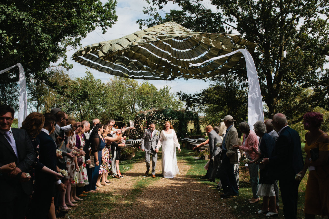 A bride and groom walk under a confetti tunnel at their woodland wedding ceremony at The Oak Grove in North Kent