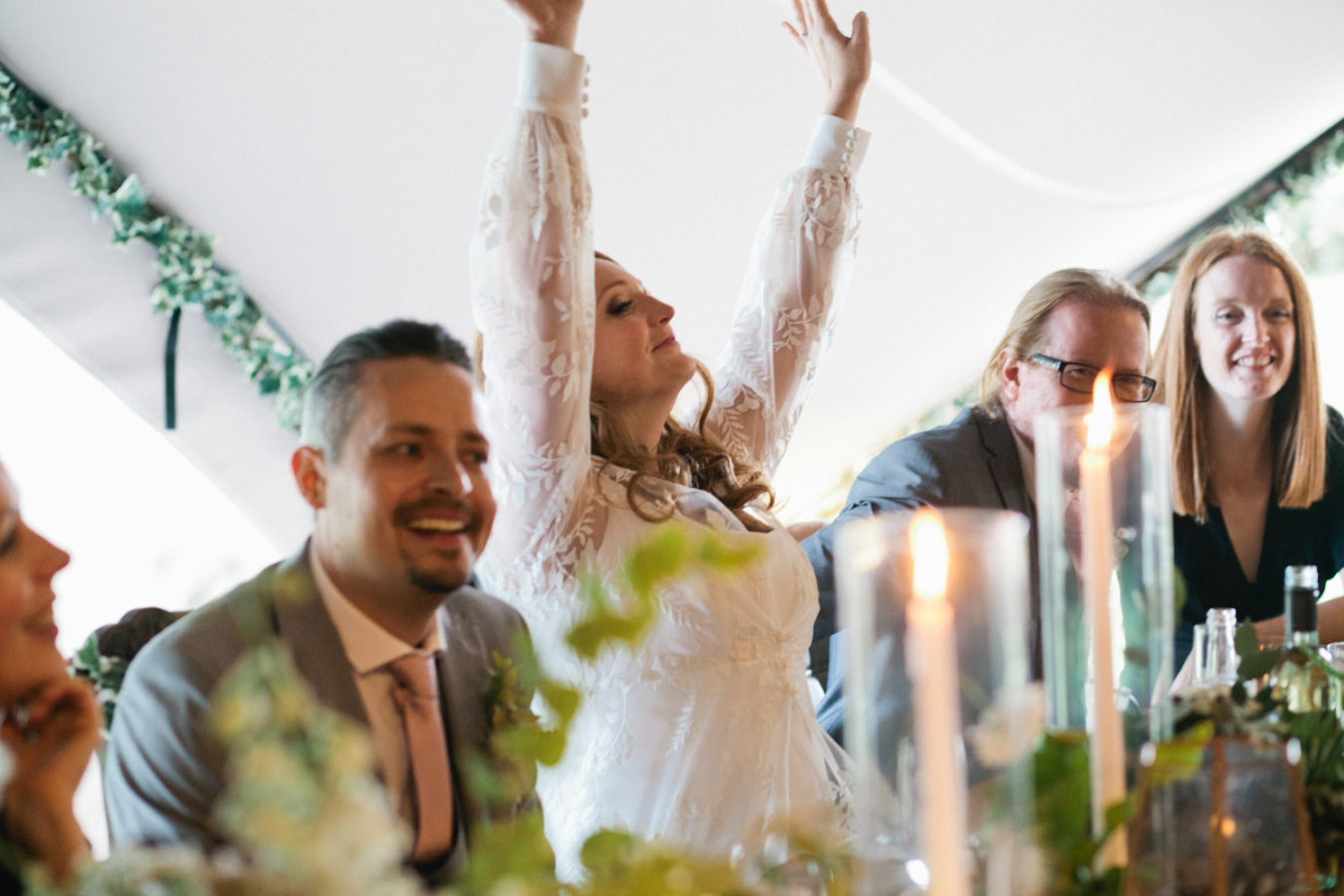 A bride holds her arms in the air with glee during the speeches at The Oak Grove wedding venue in North Kent