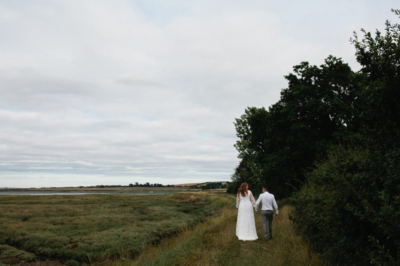 A bride and groom walk away from the photographer down the tow path at The Oak Grove Wedding venue in North Kent