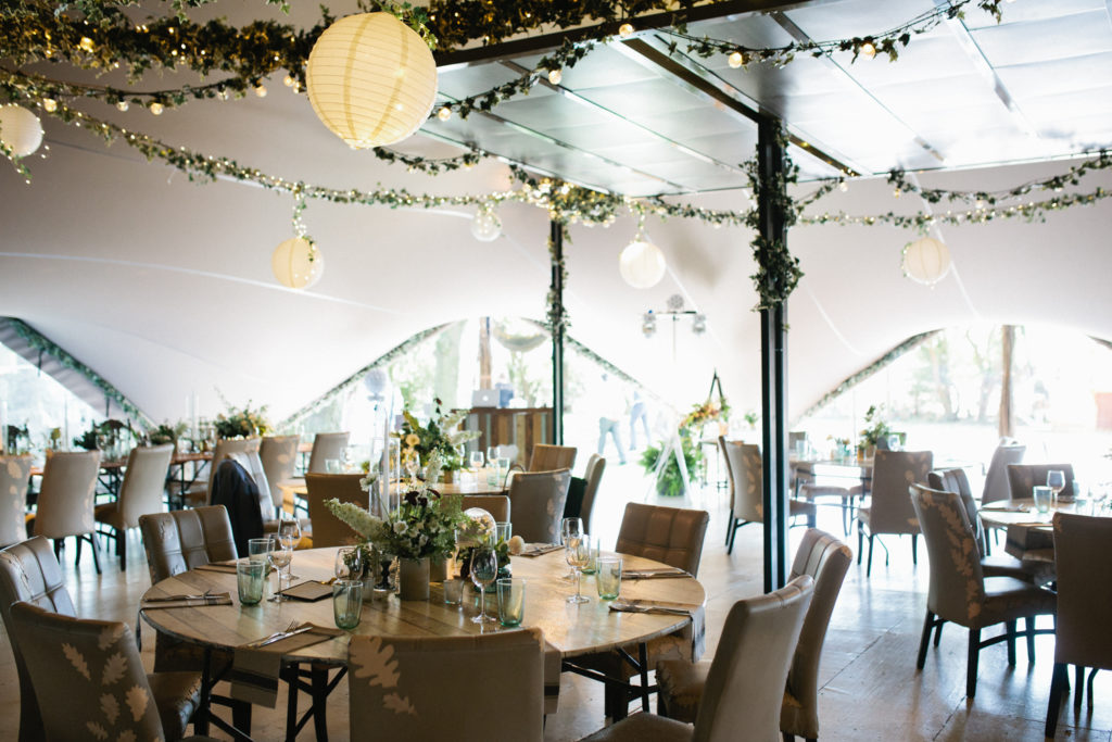 A beautifully set up marquee for a wedding breakfast at The Oak Grove wedding venue. The tables are set with lots of flowers and ferns.
