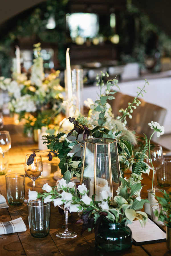 A table with a gorgeous display of ferns and glassware at The Oak Grove wedding venue/