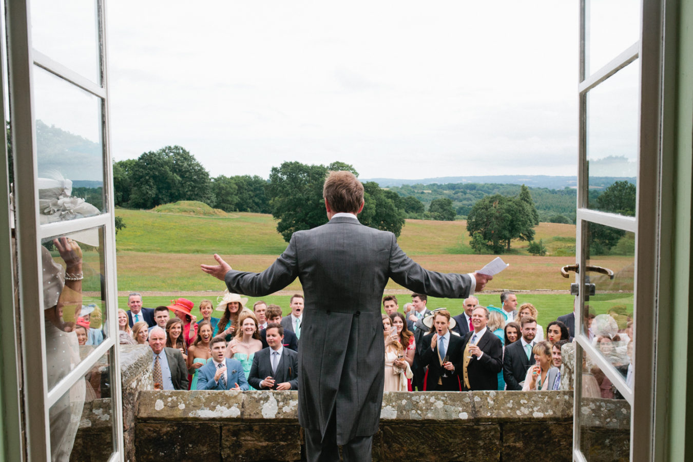 The father of the bride gives a speech on the back steps at Wadhurst Castle photographed by Sussex and Kent wedding photographer Matilda Delves