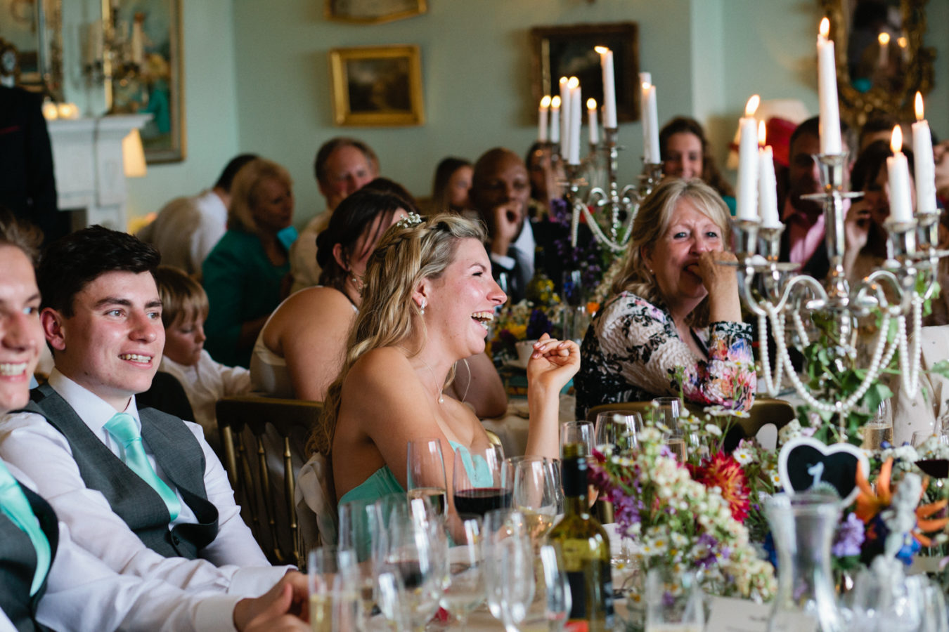 A bridesmaids laughting during the speeches at a Wadhurst Castle wedding