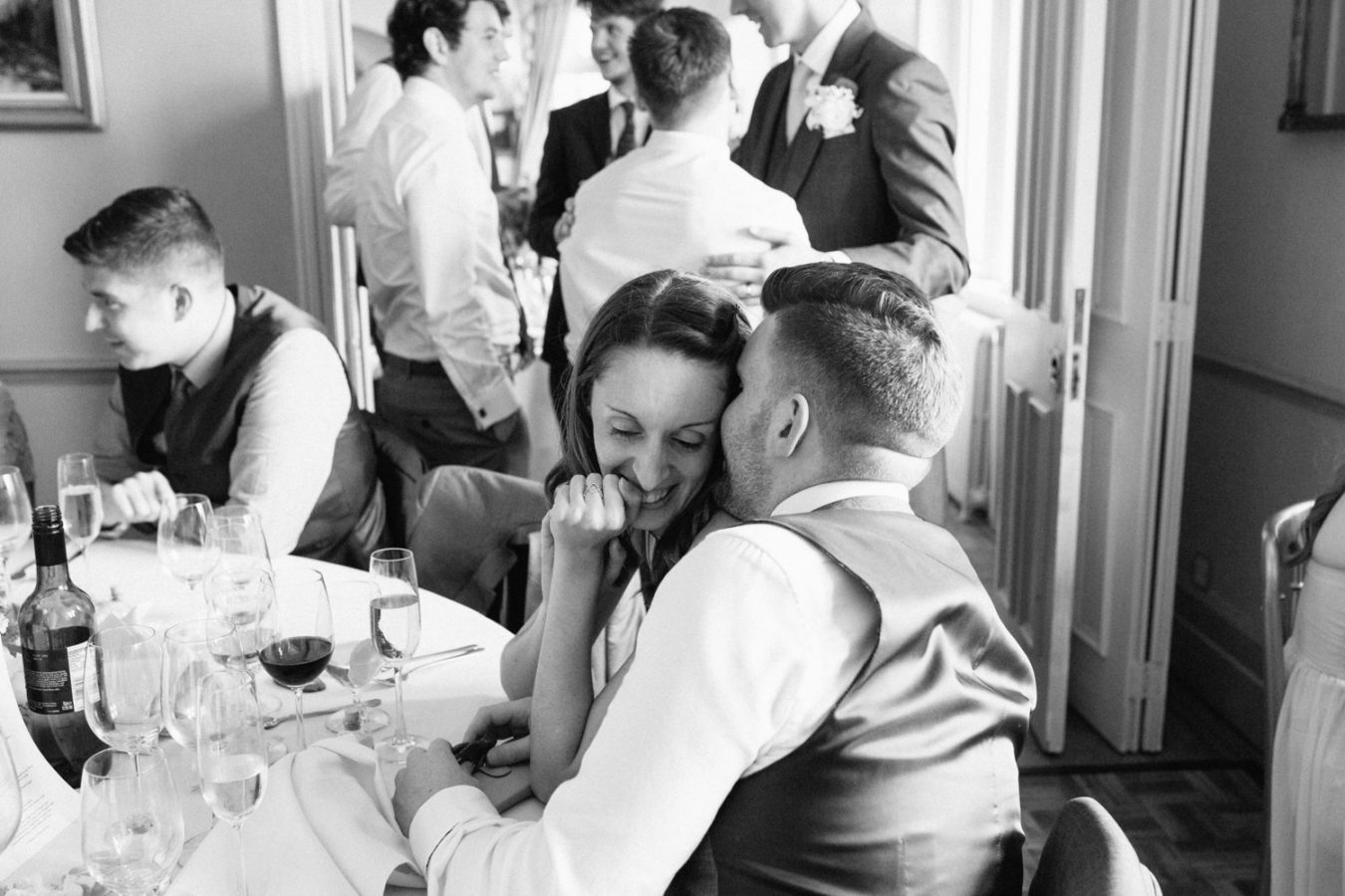 A black and white photo of wedding guest whispering to each other at a Wadhurst Castle wedding