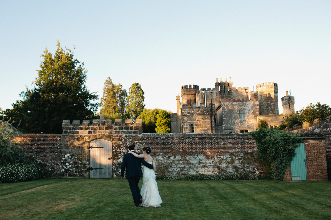A bride and groom walking on the lawn at Wadhurst Castle