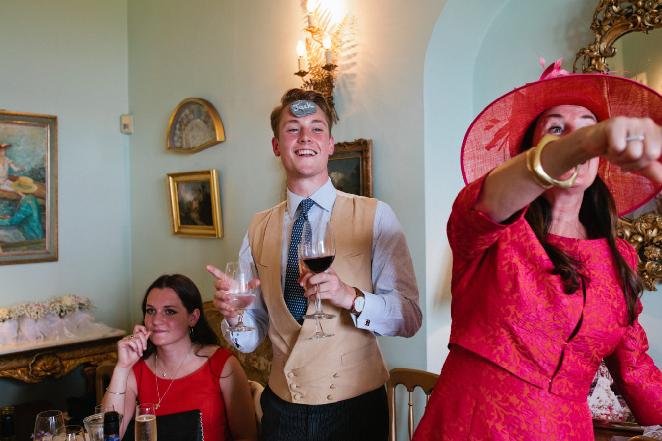 A young man wedding guest messing around before the speeches at a Wadhurst Castle wedding