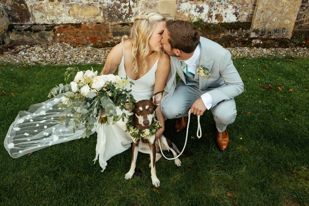 A bride and groom kissing outside of the Church in Bendenden after their wedding