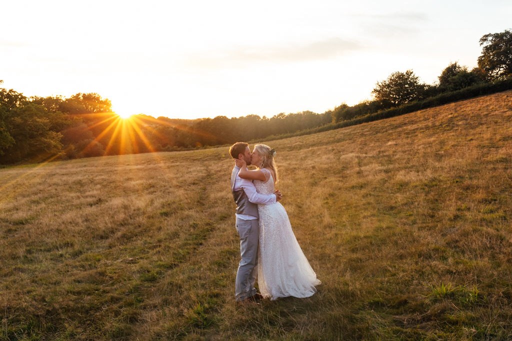 A bride and groom kissing at sunset at their The Oak Barn Frame Farm Benenden Wedding