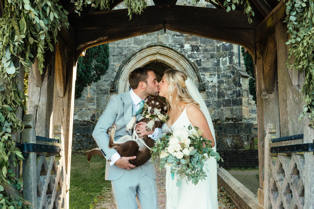 A bride and groom kissing under an arch at Benenden Church while holding their pet dog