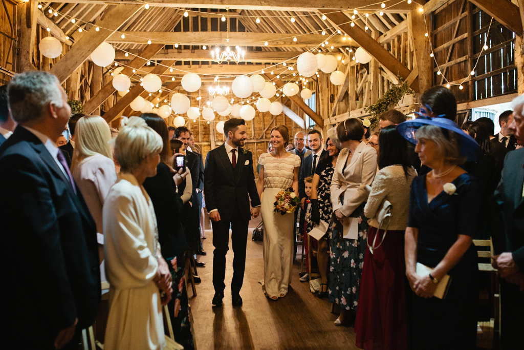 A bride and groom walk down the aisle at their The Great Barn Rolvenden wedding