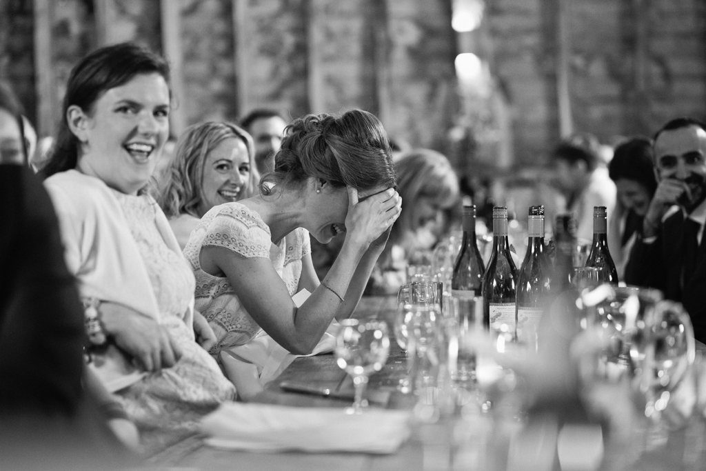 A bride looking embarrassed during the speeches during her barn wedding in Kent