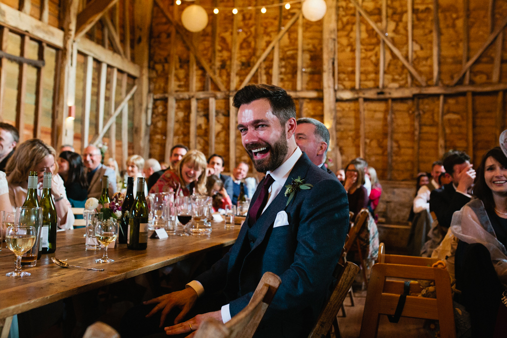 A groom laughting at speeches during his barn wedding in Kent