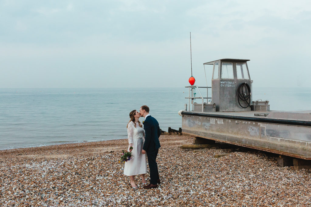A bride and groom kissing in the beach in Whitstable after their East Quay wedding
